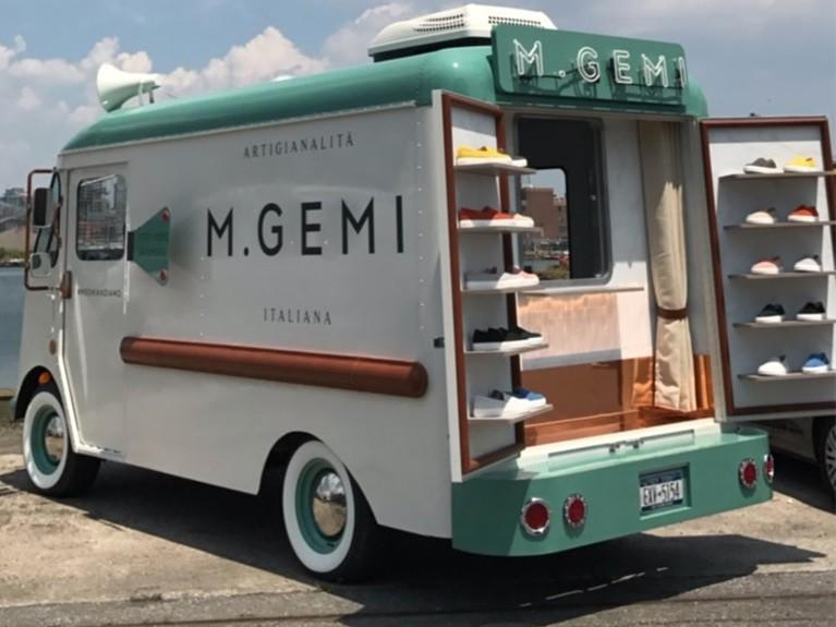 Vintage teal & white M.Gemi brand truck with it's doors open showcasing shoes.