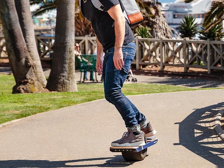 Male riding the latest skateboard innovation with helmet and backpack