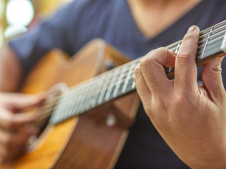 Person playing the acoustic guitar