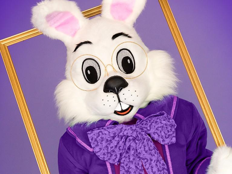 white Easter bunny wearing glasses and purple suit holding a gold picture frame