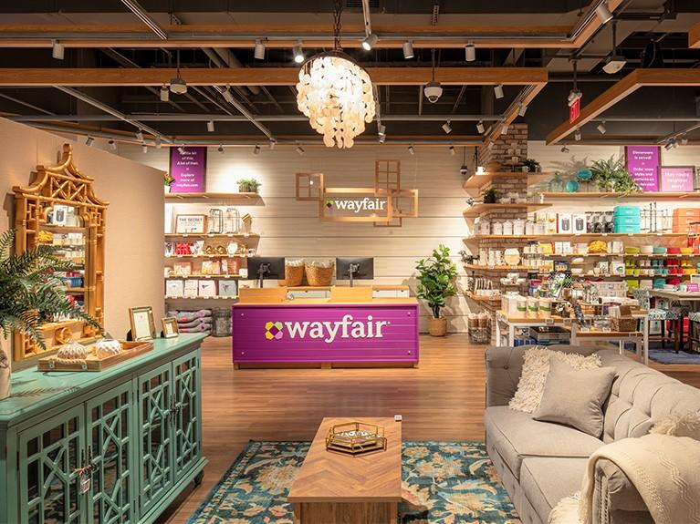 Home furnishings surrounding purple cash register station with white text reading Wayfair