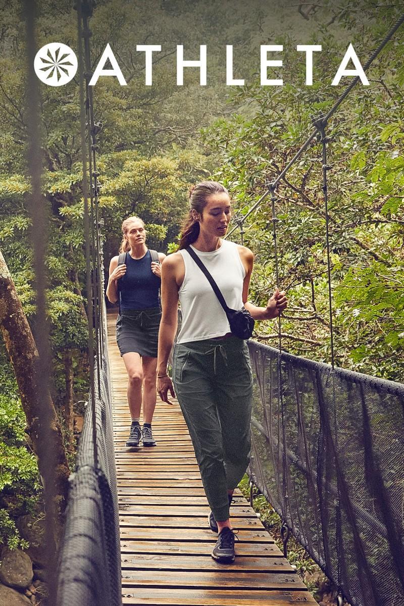 two women walking across a bridge