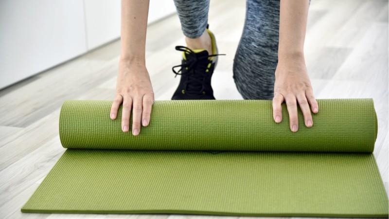 image of women in sneakers rolling up a work out mat