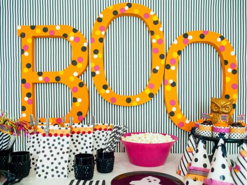 Large boo sign that is orange on a wall that is decorated with orange and black decorations.