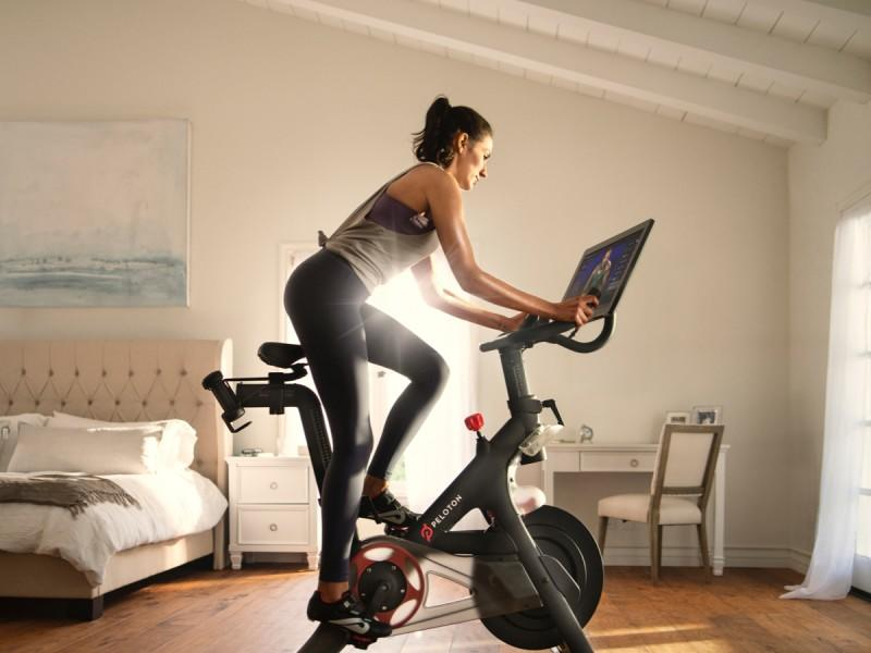 person on a bike with a live class in front of them on a screen
