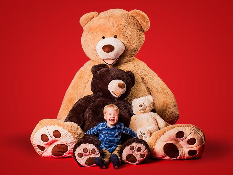 red background with three stuffed bears and a small child