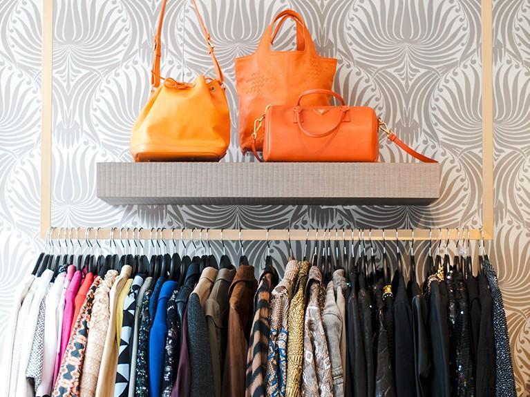 Rack of colorful clothes and a shelf of orange handbags