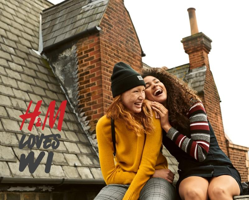 Two girls sitting on a roof top laughing
