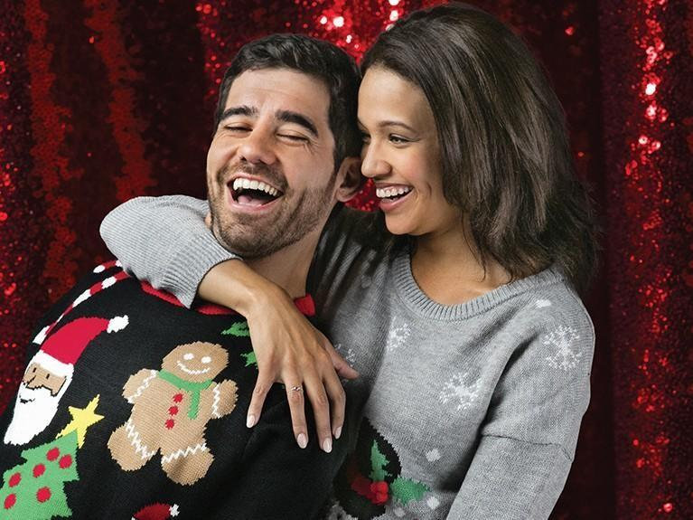 Couple wearing ugly holiday sweaters