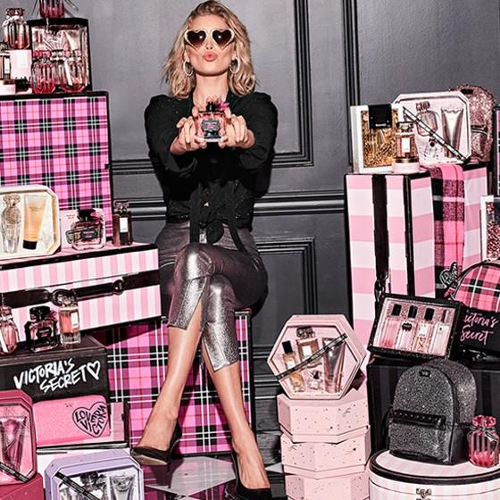 Woman with heart sharped sunglasses and sparkly pants sitting on top of a pile of suitcases and gift boxes with fragrance bottles.