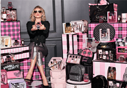 Woman with sparkly sunglasses surrounded by pink and black wrapped gifts and perfume bottles.