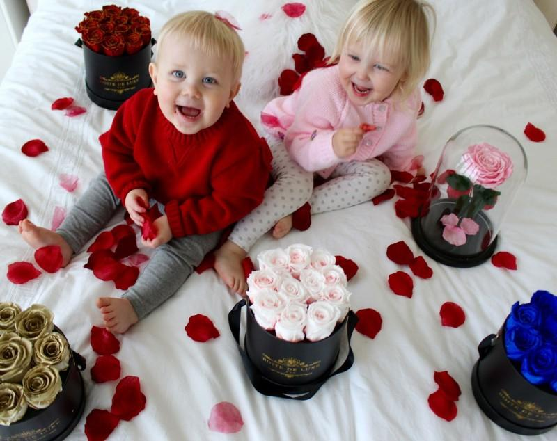 Two young children on bed with Boite de Luxe roses.