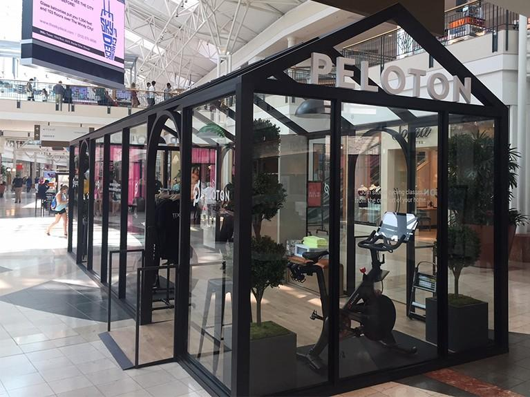 Photo of the glass Peloton showroom in the middle of the mall center court.