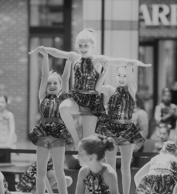 black and white picture of three girls, the girls on the sides are holding the girl in the middle up in the air.