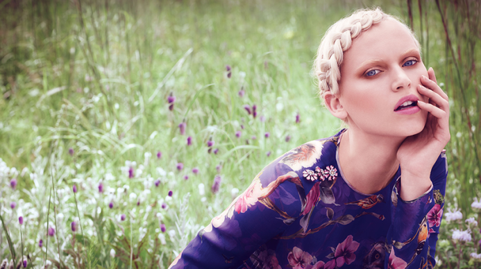woman in a field with blonde braided hair in a floral dress.
